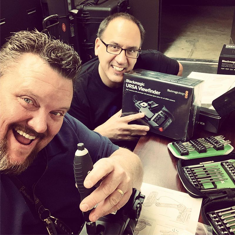 Two men smiling and holding video equipment.